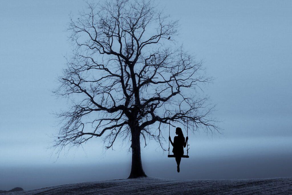 Naine kiikumas puu juures